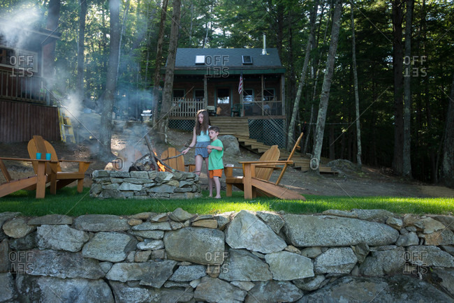 Brother and sister poke sticks into a fire near their cabin in the woods