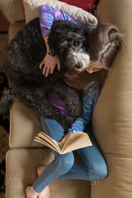 Girl snuggles with her dog as she reads on couch