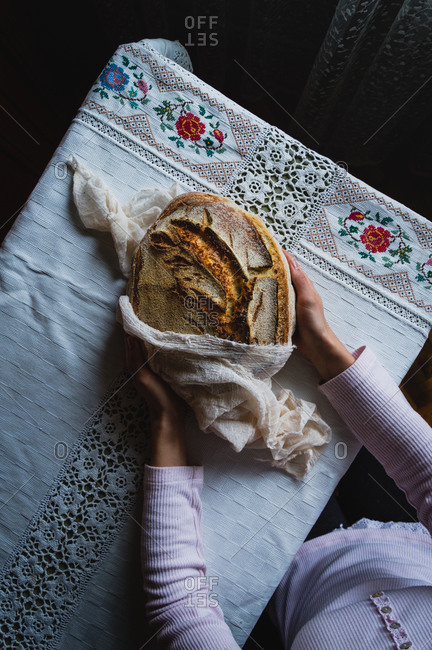 Anonymus young woman puting homemade sourdough bread on the table