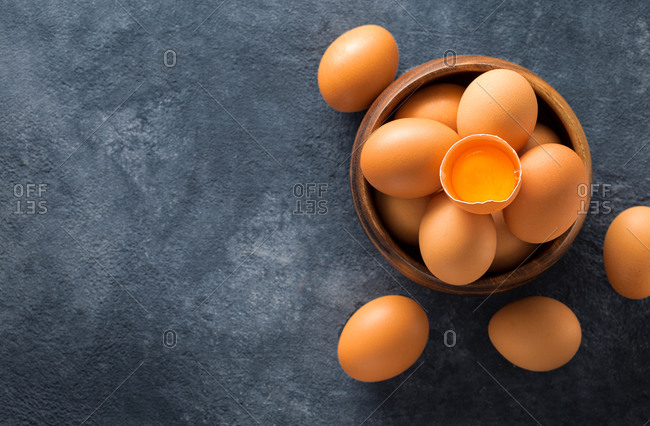 Fresh organic brown eggs in wooden bowl with yolk on dark background top view