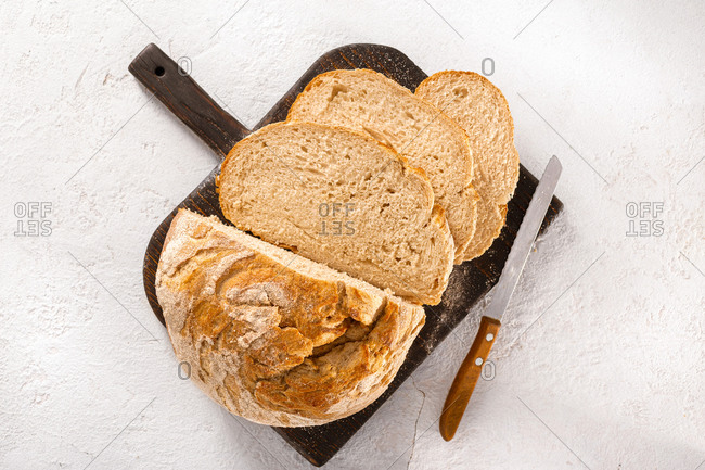 Sliced fresh homemade bread on wooden cutting board top view