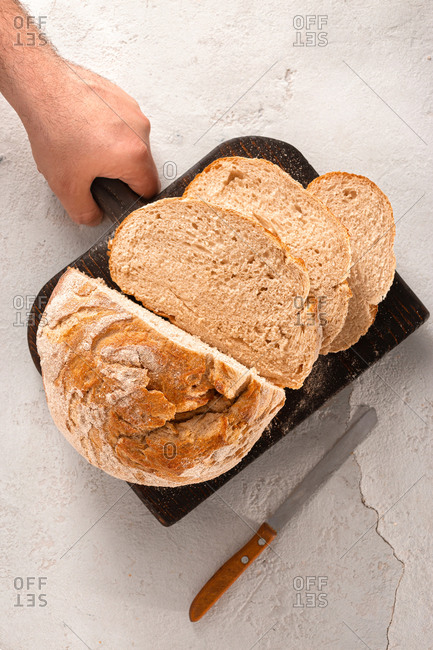 Man hand holding chopping board with sliced homemade bread on white background top view