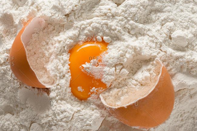 Broken egg in flour top view