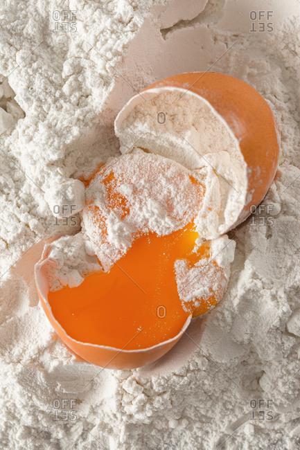 Broken egg in flour close up top view