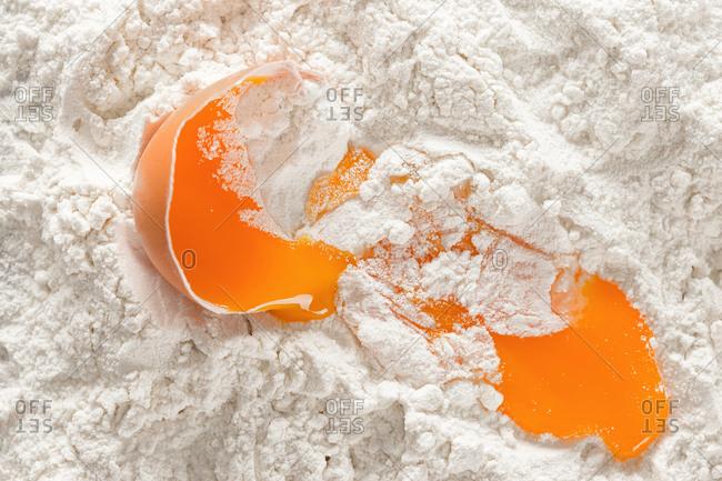 Broken egg in flour overhead view