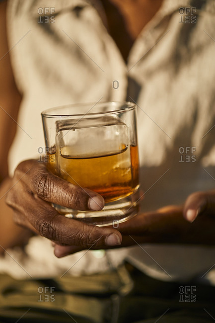 Holding a whiskey drink