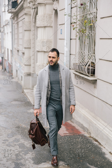 Young businessman with backpack walking in the street.