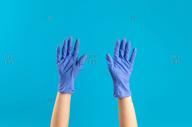 Doctor putting on blue latex gloves