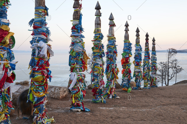 February 8, 2019: Colorful decorated Buddhist shaman poles above Lake Baikal on Olkhon island at sunrise in winter, Siberia, Russia, Eurasia