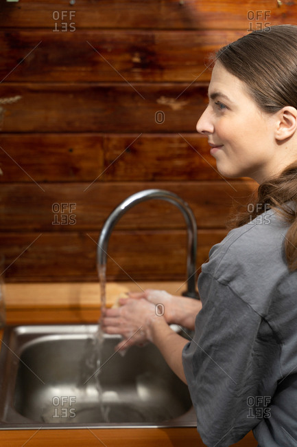 Woman washes her hands with soap to disinfect from the covid-19 virus after going to the store