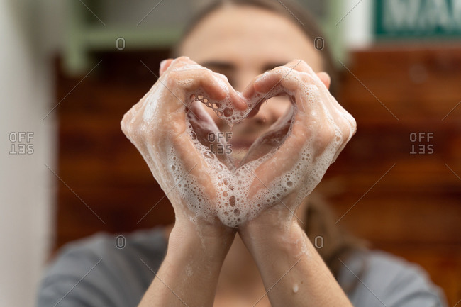 Woman makes a heart with her hands in soap where it is safe at home