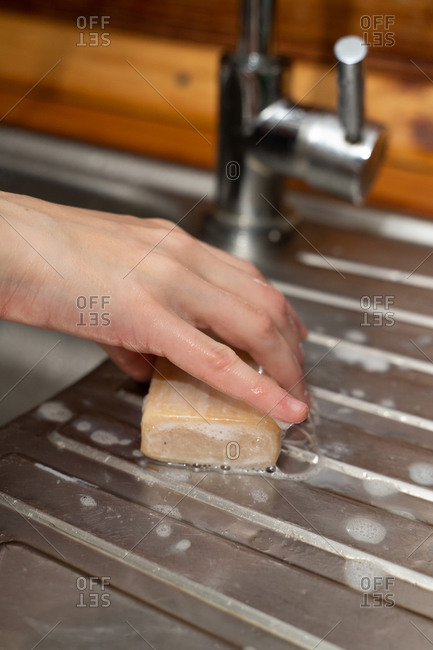 Woman holds soap in hands on near a sink