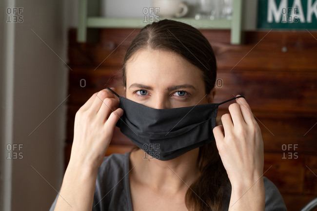Woman puts a silk mask on her face to protect herself from the covid-19 virus