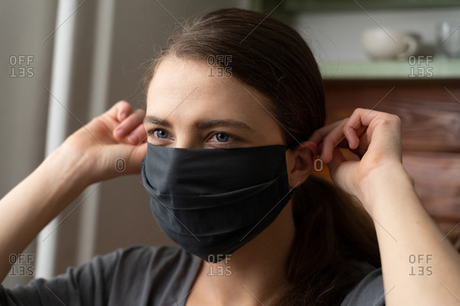 A woman holds a protective silk mask on her face to protect herself from the covid-19 virus