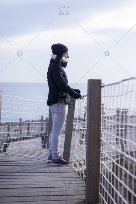 Back view of a woman standing on gangway while looking away to the sea thinking about future