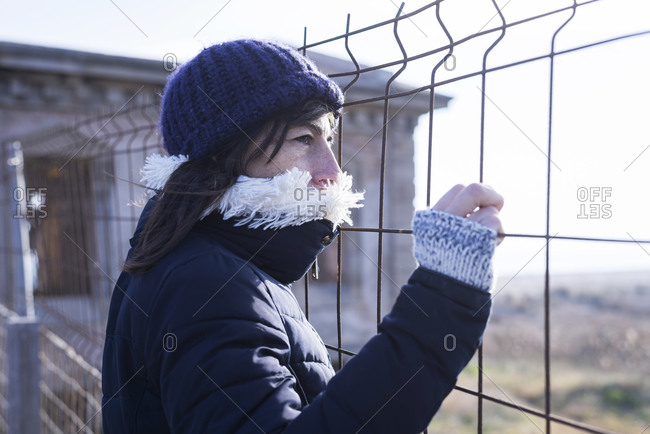 Back view of a woman with cap leaning on a metallic fence while looking away pensive at sunset