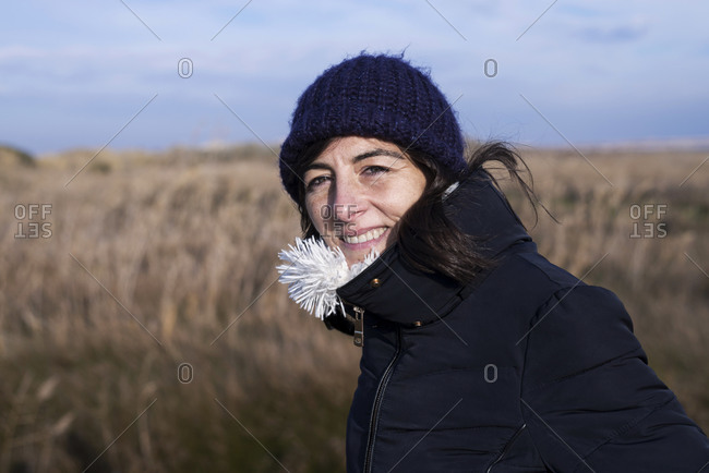 Image of young woman wearing hat and scarf walking outdoors