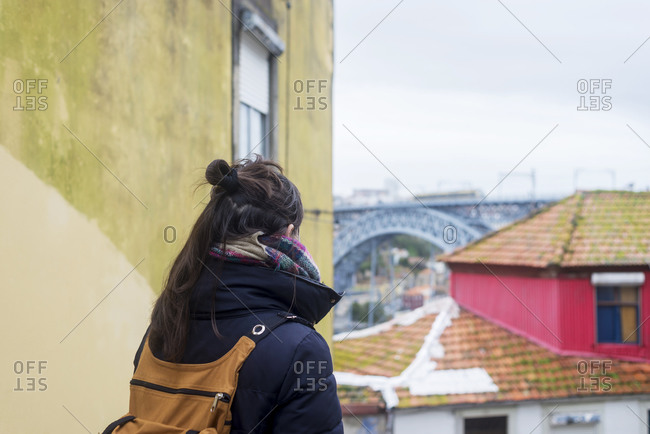 Rear view of young backpacker woman enjoying Porto sight in winter time, Portugal