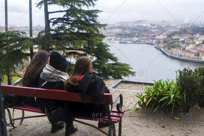 Back view of three unrecognizable girls sitting on a bench admiring Porto city from high