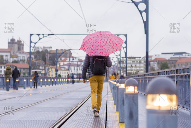 Rear view of a man walking with umbrella on rainy day in historical center of Porto, Europe