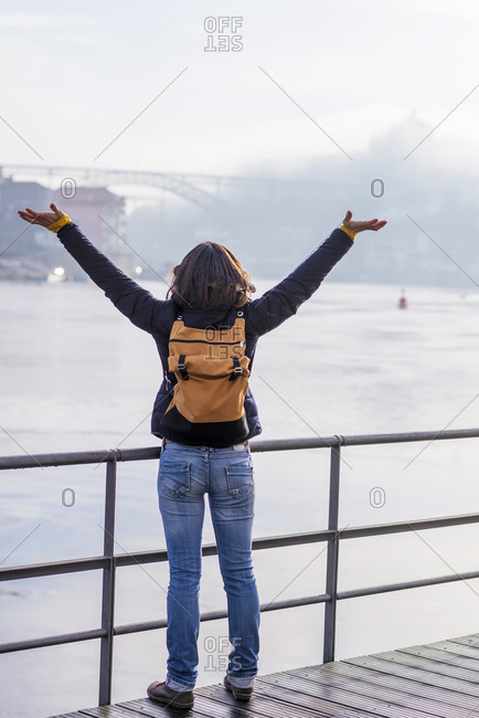 Back view of a backpacker woman arms raised on river promenade against Duoro River in Porto
