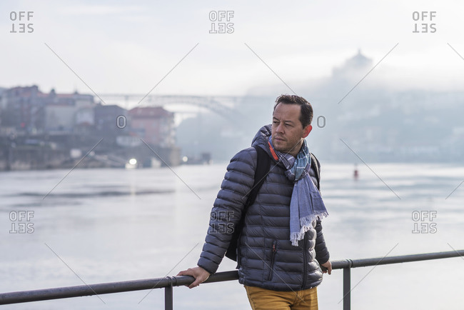 Portrait of a attractive bearded man with scarf leaning on railings against Duoro River in Porto