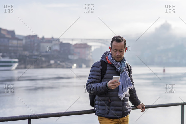 Portrait of a attractive bearded man with scarf leaning on railings against Duoro River in Porto while using mobile phone