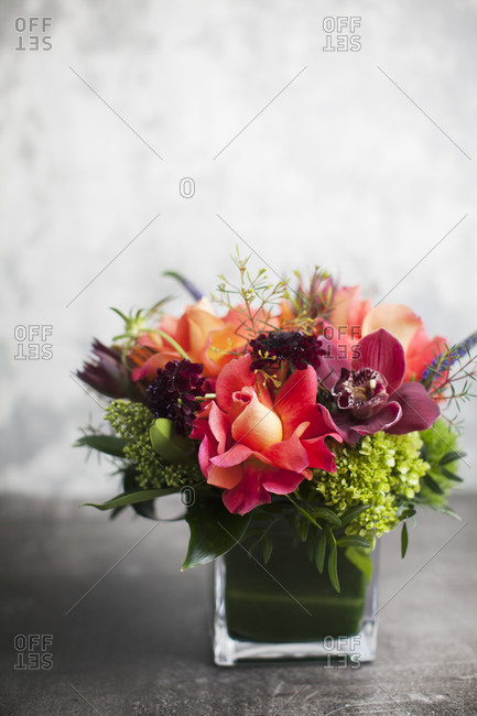 Floral arrangement with red roses and orchids