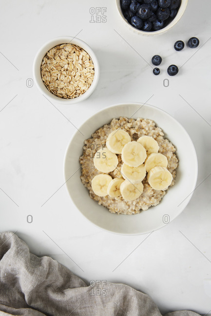 Bowl of porridge topped with banana,  a bowl of oats and a  bowl of blueberries on white marble countertop