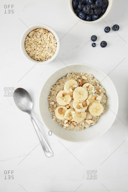 Bowl of porridge topped with banana and almonds,  a bowl of oats and a  bowl of blueberries on white marble countertop