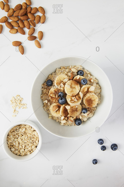 Bowl of porridge topped with banana, blueberries, almonds and cinnamon, a bowl full of oats and almonds and blueberries scattered on white marble countertop