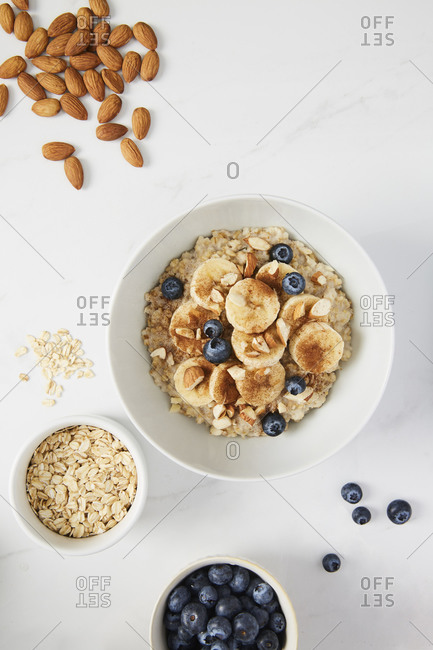 Bowl of porridge topped with banana, blueberries, almonds and cinnamon, a bowl full of oats and berries along with almonds and blueberries scattered on white marble countertop