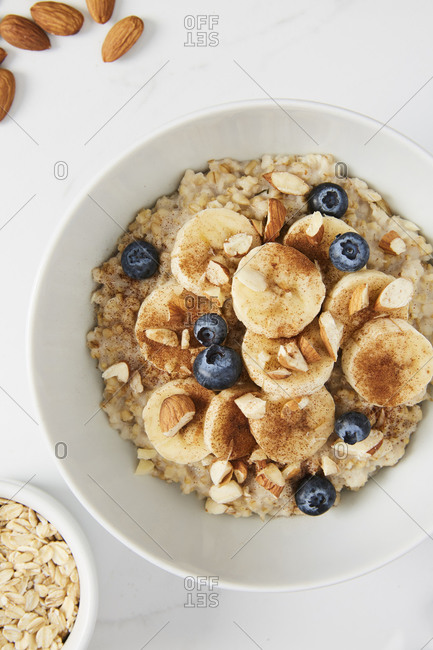 Bowl of porridge topped with banana, blueberries, almonds and cinnamon, a bowl full of oats