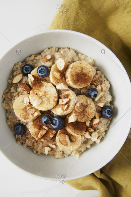 Bowl of porridge topped with banana, blueberries, almonds and cinnamon on a green linen
