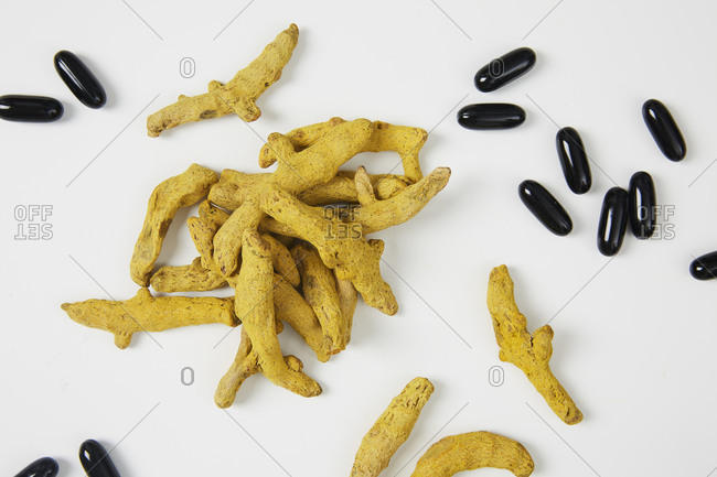 Dried turmeric root with omega 3 fatty acids soft gel on white background
