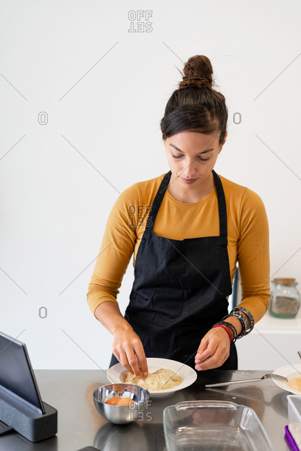 Brunette woman streaming a cooking class with some homeade recipes from her kitchen