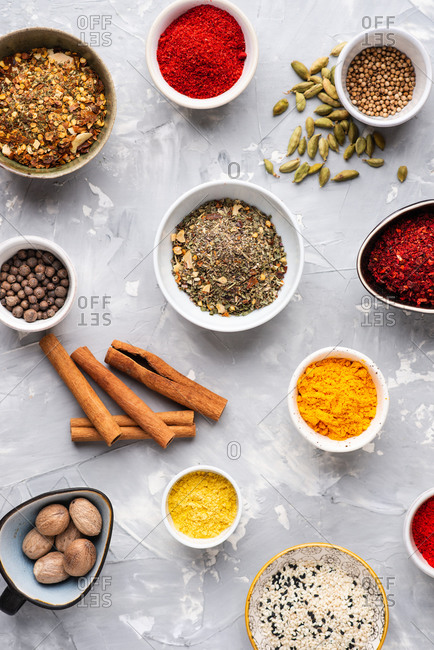 Overhead view composition of colorful assorted spices over gray background