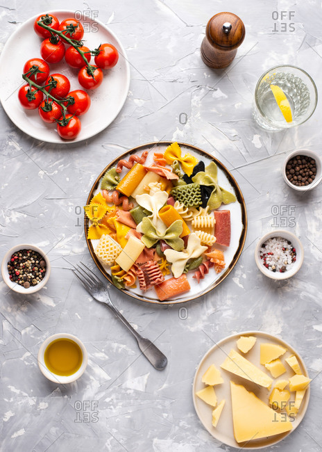 Overhead view of two plates with colorful Italian pasta served with parmesan cheese over gray background