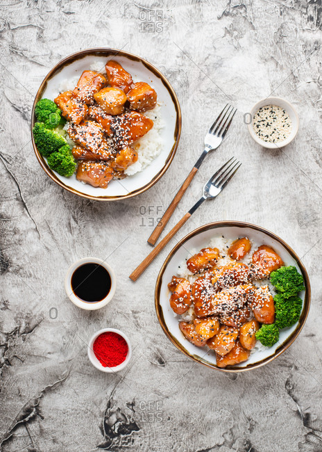 Overhead view of two bowls with rice and sticky honey fried chicken bites with sesame seeds and broccoli