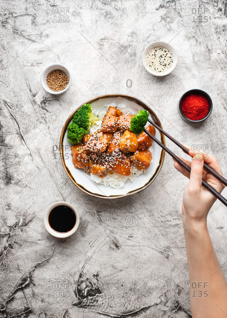 Overhead view of bowl with rice and sticky honey fried chicken bites. Female hand holding chopsticks