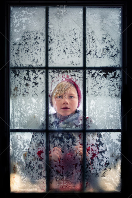 A young boy looking in through a cold, frosty window