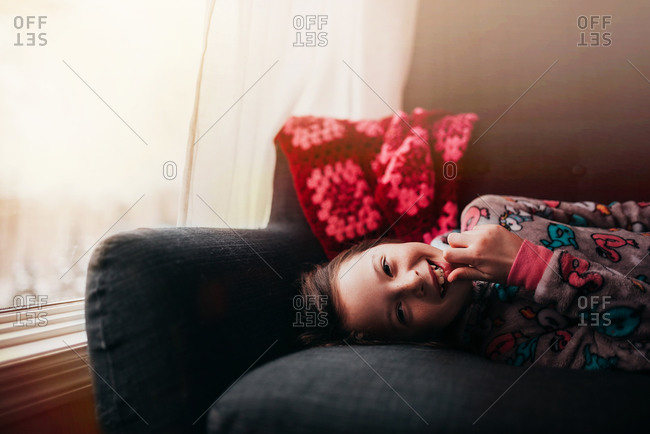 Portrait of a young happy girl laying on a sofa by the window