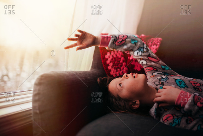 Portrait of a young happy girl laying on a sofa reaching toward window