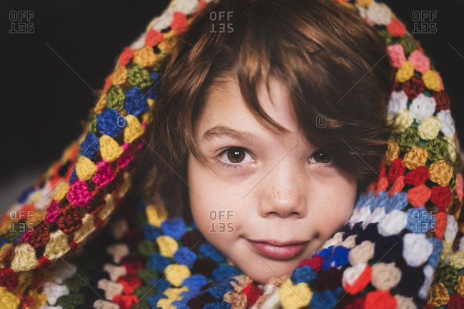 A portrait of a young boy wrapped in a colorful blanket