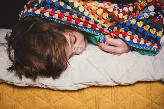 Young boy sleeping with a colorful blanket wrapped around him