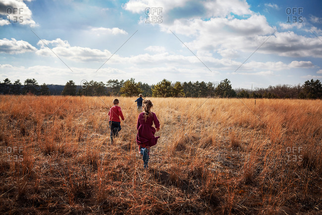 Three young kids outside in an open field