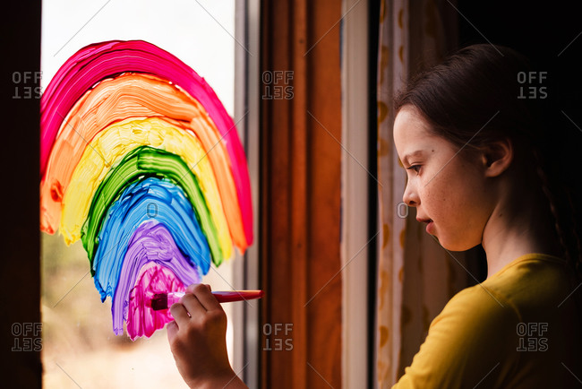 Young girl painting rainbows on a window to support Stay-at-Home