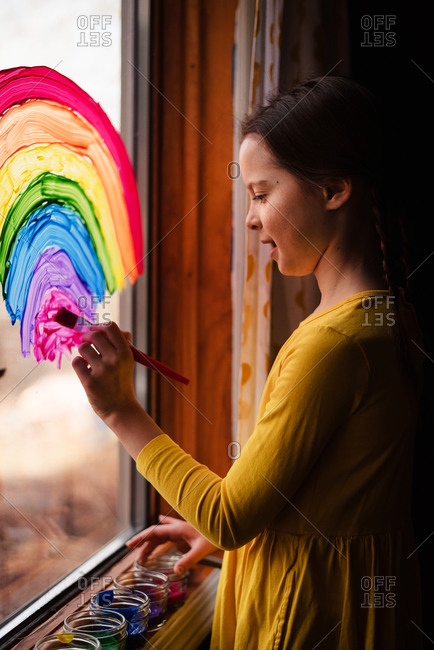 Brunette girl painting rainbows on a window to support Stay-at-Home