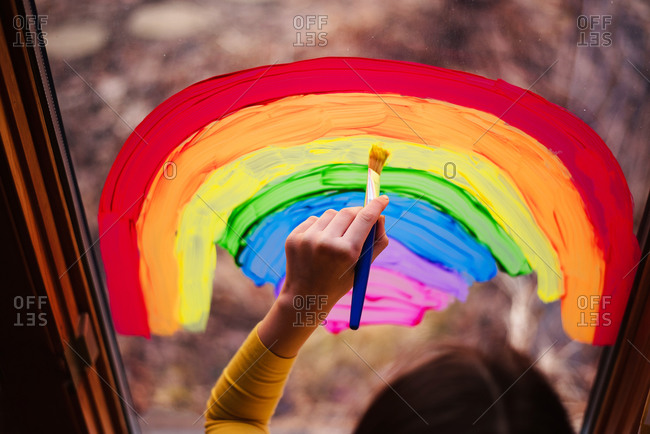 Overhead view of young girl painting rainbows on a window to support Stay-at-Home