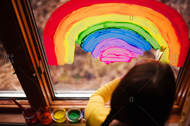 Top view of a young girl painting rainbows on a window to support Stay-at-Home